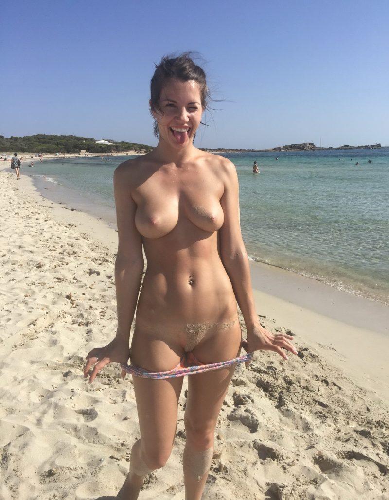 Pokazuje cipeczkę na plaży